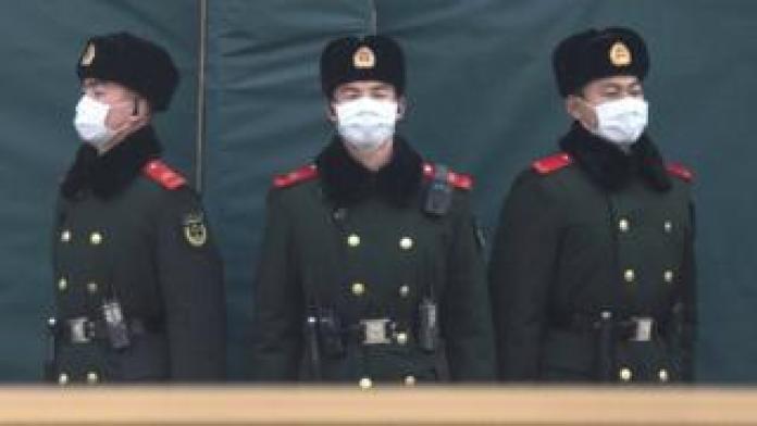 Chinese policemen wearing masks