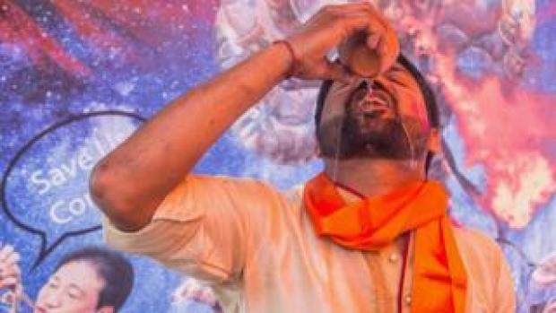 "Man drinking cow urine at a ""gaumutra"" event in Delhi"