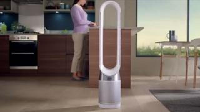 A bladeless fan stands in the centre of a kitchen , with no power cord to be seen