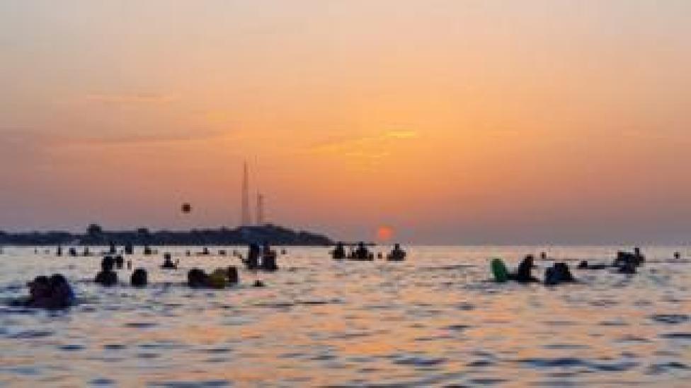 People bathe in the Mediterranean sea water off a beach in Libya's capital Tripoli near sunset on August 18, 2020.