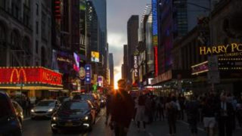 People take a look at the phenomenon known as Manhattanhenge on 42nd Street on May 30, 2018 in New York City