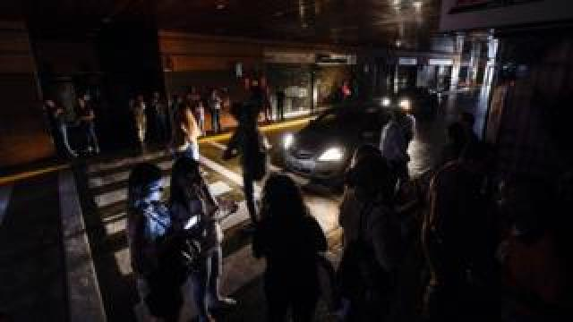 People wait in a shopping centre car park in Caracas as the city is hit by a blackout