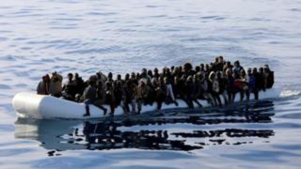 Migrants are seen in a rubber dinghy as they are rescued by Libyan coast guards off the coast of Libya, 15 January 2015