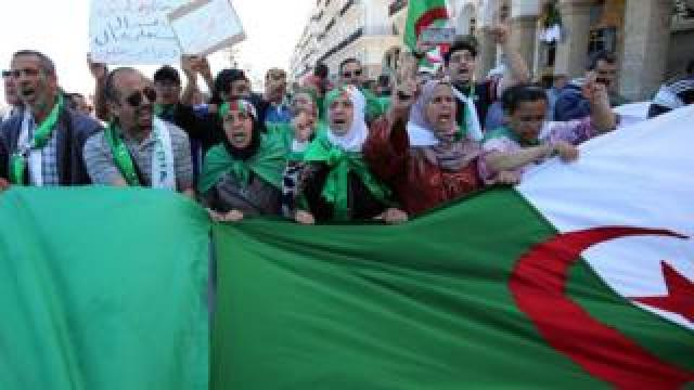 Algerian protesters hold a large flag in the capital Algiers
