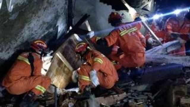 Rescuers search for survivors in the rubble of a building in Yibin, in China's southwest Sichuan province early on June 18, 2019