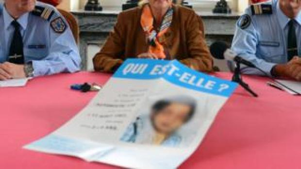 "Police and a prosecutor present a leaflet to the media with a picture of the girl and a message reading ""Who is she?"""