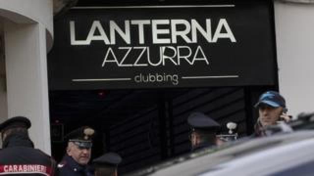 Police officers stand in front of the entrance of the Lanterna Azzurra concert hall in Corinaldo