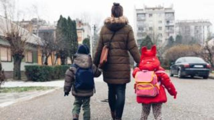 Woman walking with two children