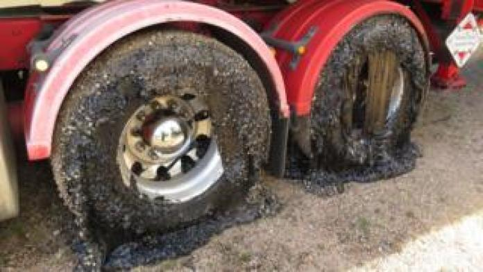Two wheels of a truck coated in tar