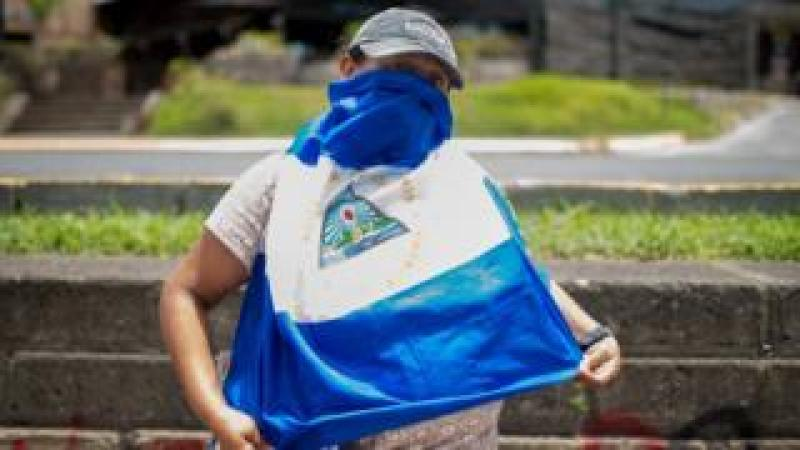 A protester in Nicaragua, who gives Claudia as a pseudonym, covers her face with a Nicaraguan flag