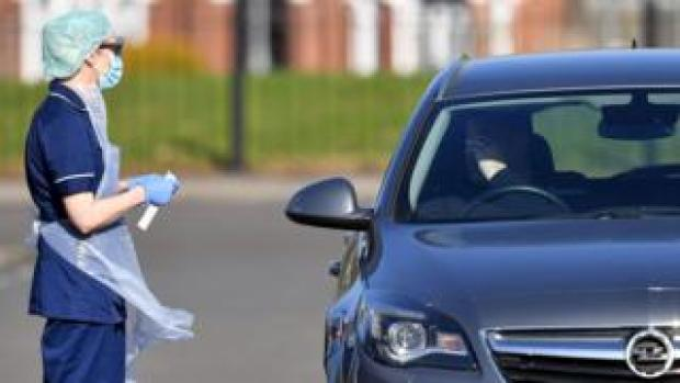 A medical staff member wearing PPE of gloves, eye protection, a face mask and an apron, prepares to test an NHS worker for the novel coronavirus COVID-19, at a drive-in facility run by Wolverhampton NHS Clinical Commissioning Group, set up in a car park in Wolverhampton, central England