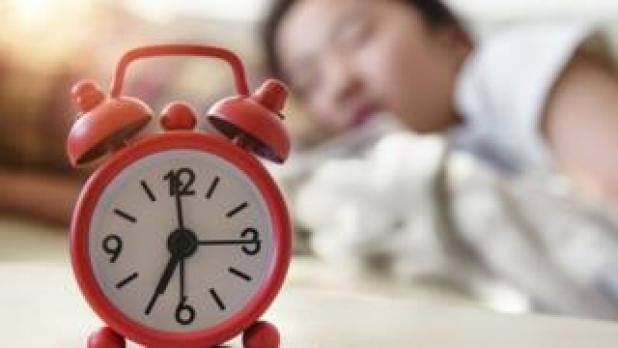 A woman asleep with an alarm clock