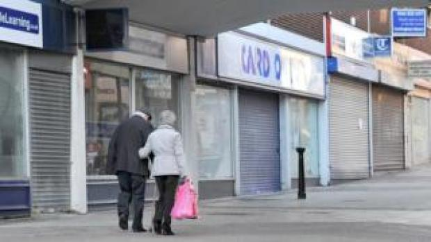 People walking past closed shops