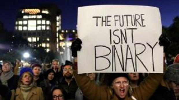 Protesters in New York. One holds a sign saying 'The future isn't binary'