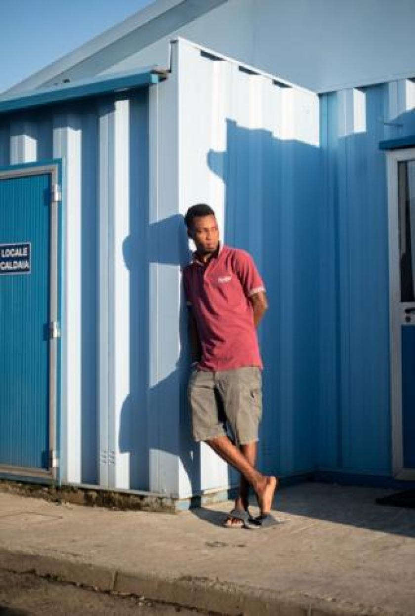 Emmanuel leans against temporary shipping containers