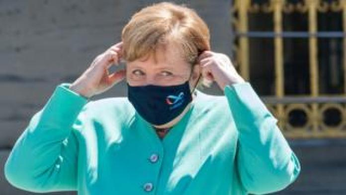 German Chancellor Angela Merkel adjusts her protective mask on her way to a Bavarian state cabinet meeting at Herrenchiemsee Island, Germany, July 14, 2020
