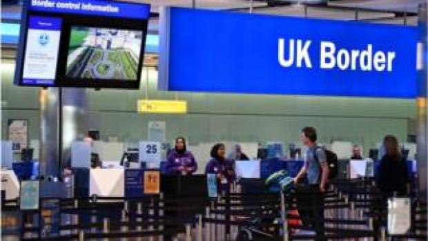 Travellers at passport control at Heathrow Airport