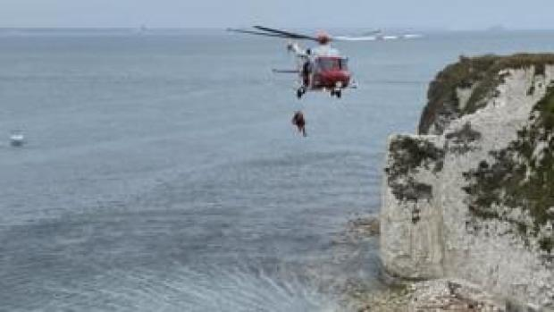 A person suspended underneath the coastguard helicopter hovering over the sea at Old Harry Rocks chalk cliffs