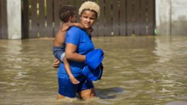 Woman carrying child wades through flooded street