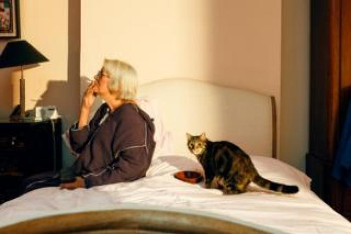 A woman sits on the bed smoking with her cat beside her
