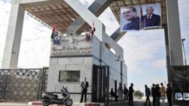 Portraits of Egyptian President Abdel Fattah al-Sisi and Palestinian leader Mahmoud Abbas hang at the Rafah border crossing with Egypt on 1 November 2017