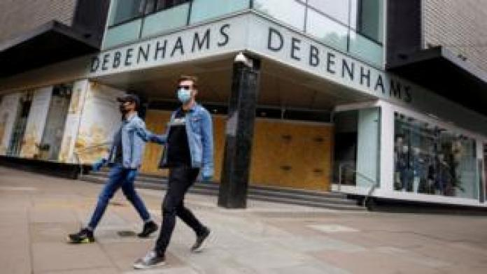 Two people wearing masks walk past an onboard Debenhams store in Oxford Street, London