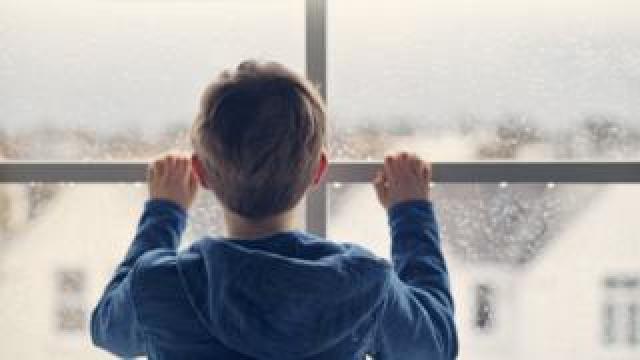 Boy stood by window