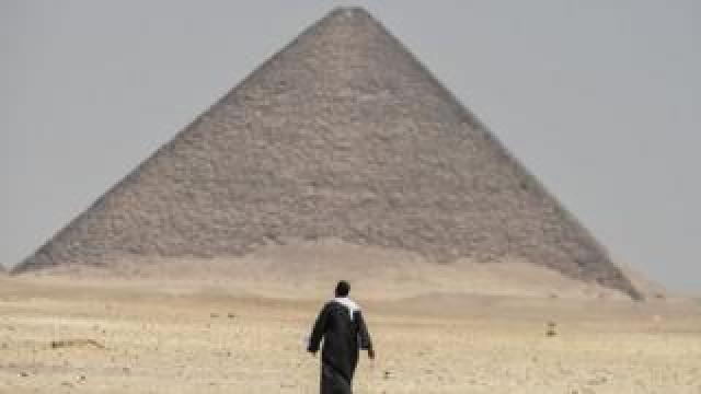 A man walks next to the Red Pyramid at Dahshur. Photo: 13 July 2019