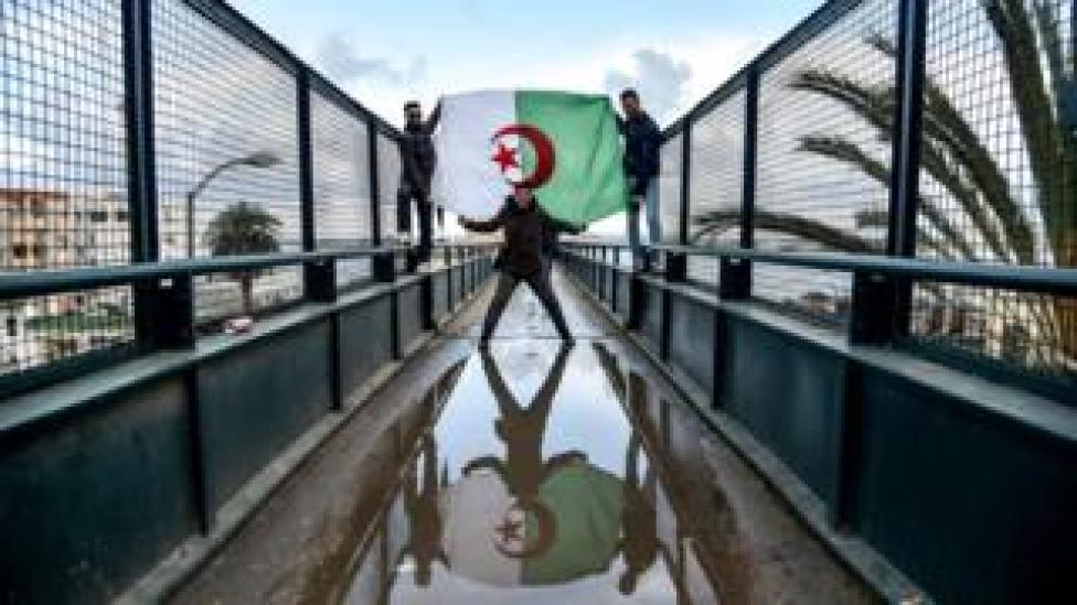 Algerians draped in the national flag take part in a demonstration against ailing President Abdelaziz Bouteflika in the capital Algiers on March 22, 2019.