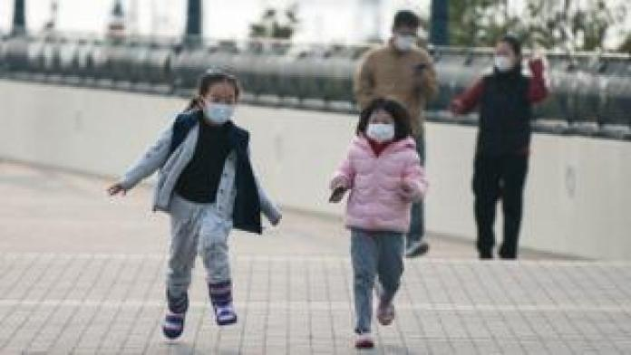 two little girls running wearing masks