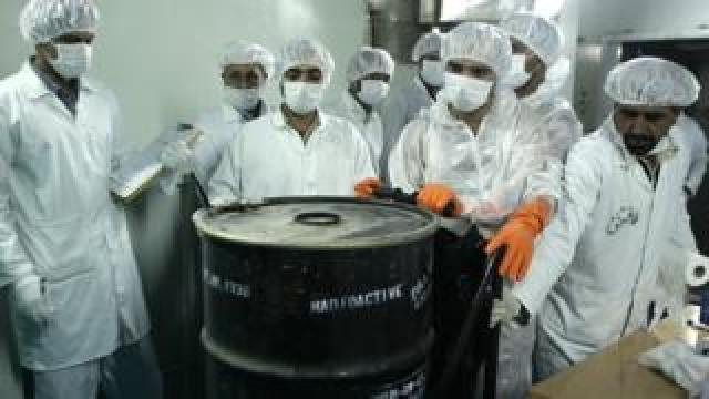 "Iranian technicians remove a container of radioactive uranium, ""yellow cake"", sealed by the International Atomic Energy Agency, to be used at the Isfahan plant. Photo: August 2005"