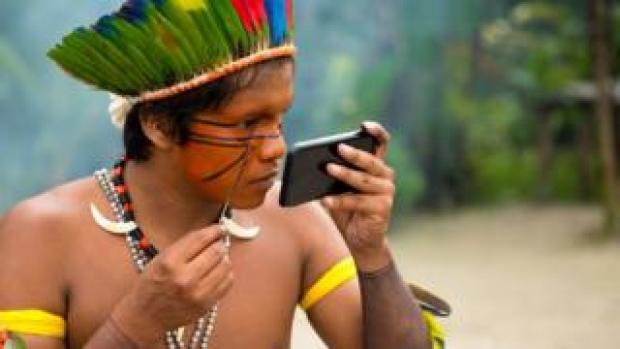 An indigenous man from the Tupi Guarani tribe in Brazil paints his face