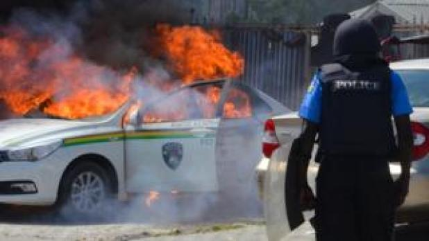 Policeman in front of burning vehicle