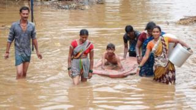 People wade through floodwaters to reach higher ground following heavy rains in Karnataka state on 8 August