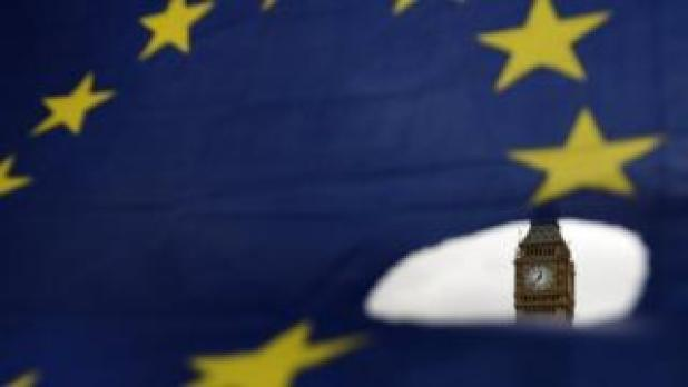 Big Ben is seen through a hole in an EU flag in London. Photo: 29 March 2017