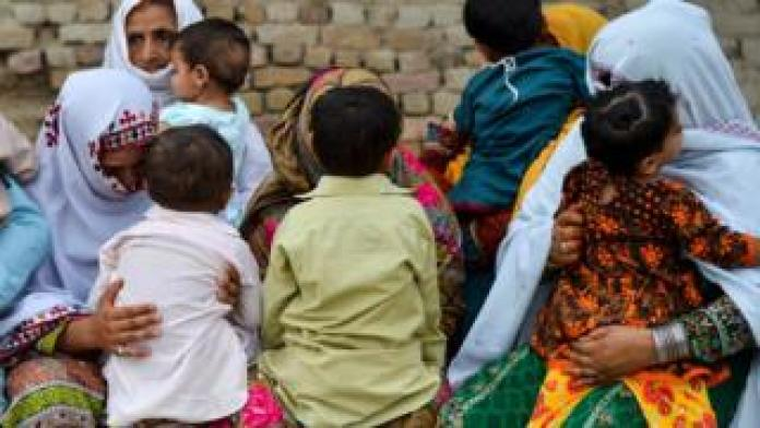 Parents nervously watch their children while they are lined up to be tested for HIV in a village near Larkana in Pakistan, in a sudden outburst among his young people
