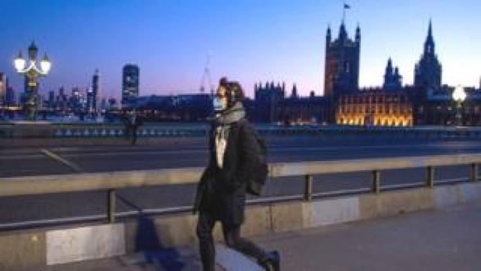 Man in mask crosses Westminster Bridge in front of the Houses of Parliament