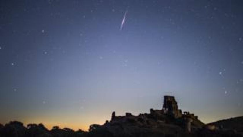 A Perseid Meteor flashes across the night sky above Corfe Castle