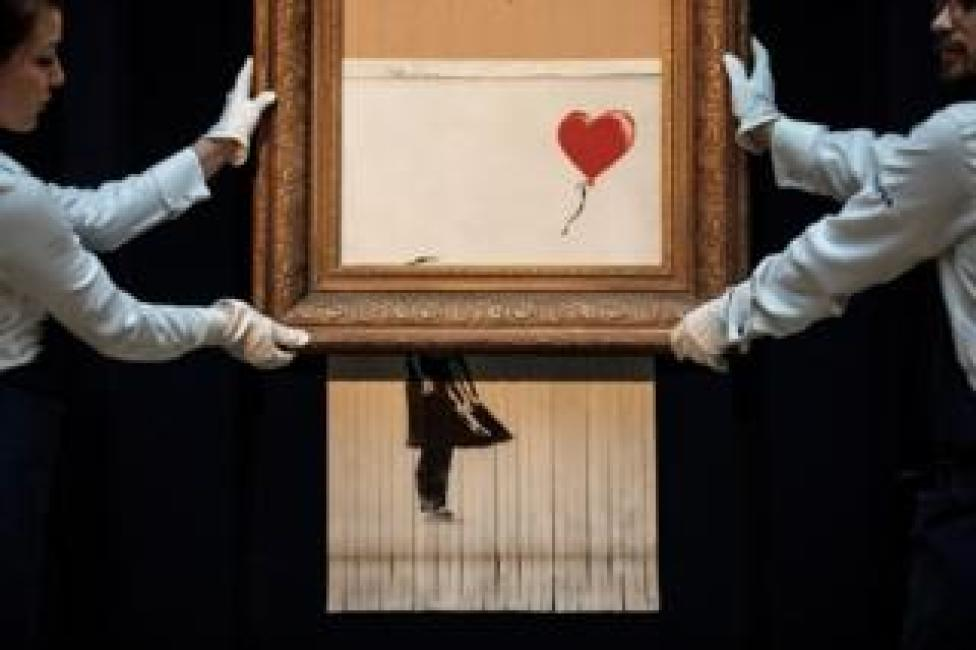 Sotheby's employees pose with Love is in the Bin by British artist Banksy