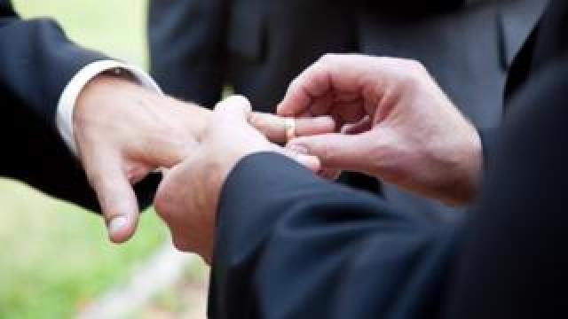 Husbands exchanging wedding rings