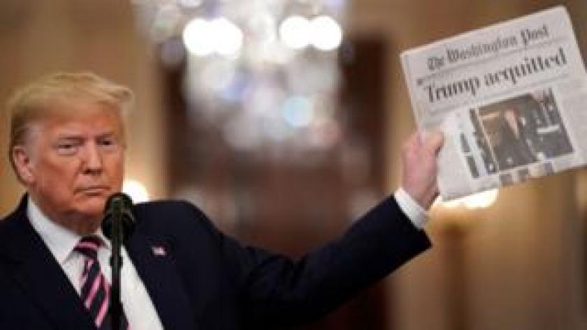 impeach Trump holds newspaper reading, 'acquitted'