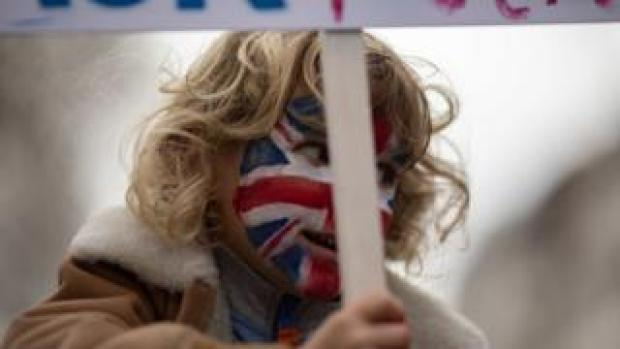 A child with a painted face holds a placard