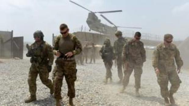 US soldiers walk by as a Nato helicopter flies overhead at a coalition base in the Khogyani district in the eastern Afghan province of Nangarhar. August 12, 2015