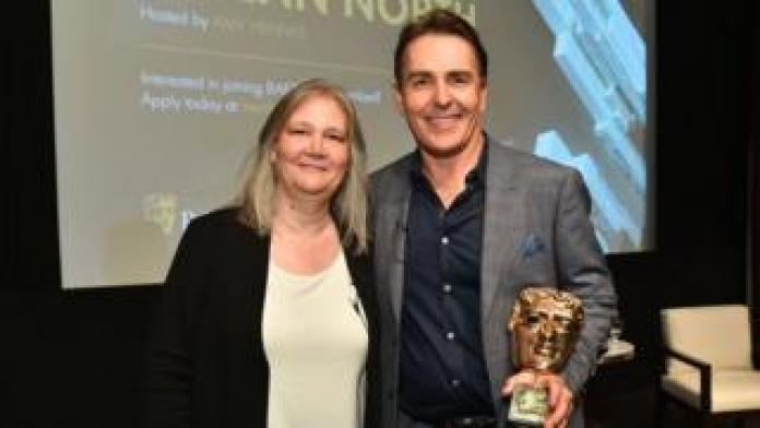 Amy Hennig and Nolan North pose with his BAFTA