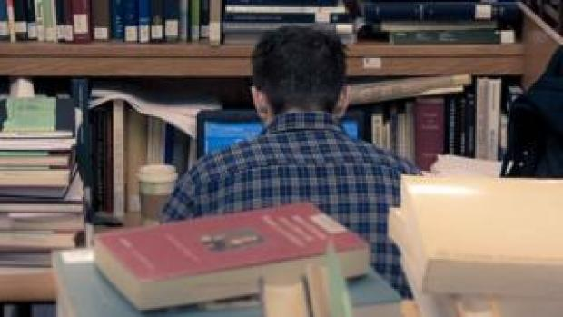 Stock picture of student surrounded by books