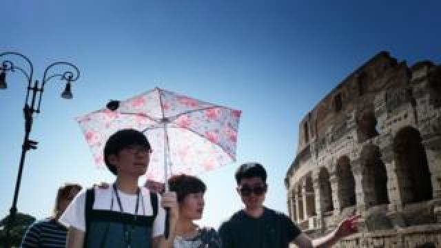 Tourists shelter from the sun with umbrellas in front of the Colosseum in Rome on June 25, 2019 during a heatwave.