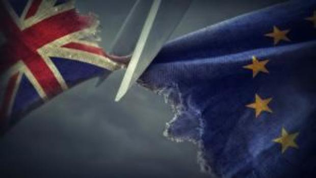 A pair of scissors cutting fabric showing the Union Jack and the EU flag