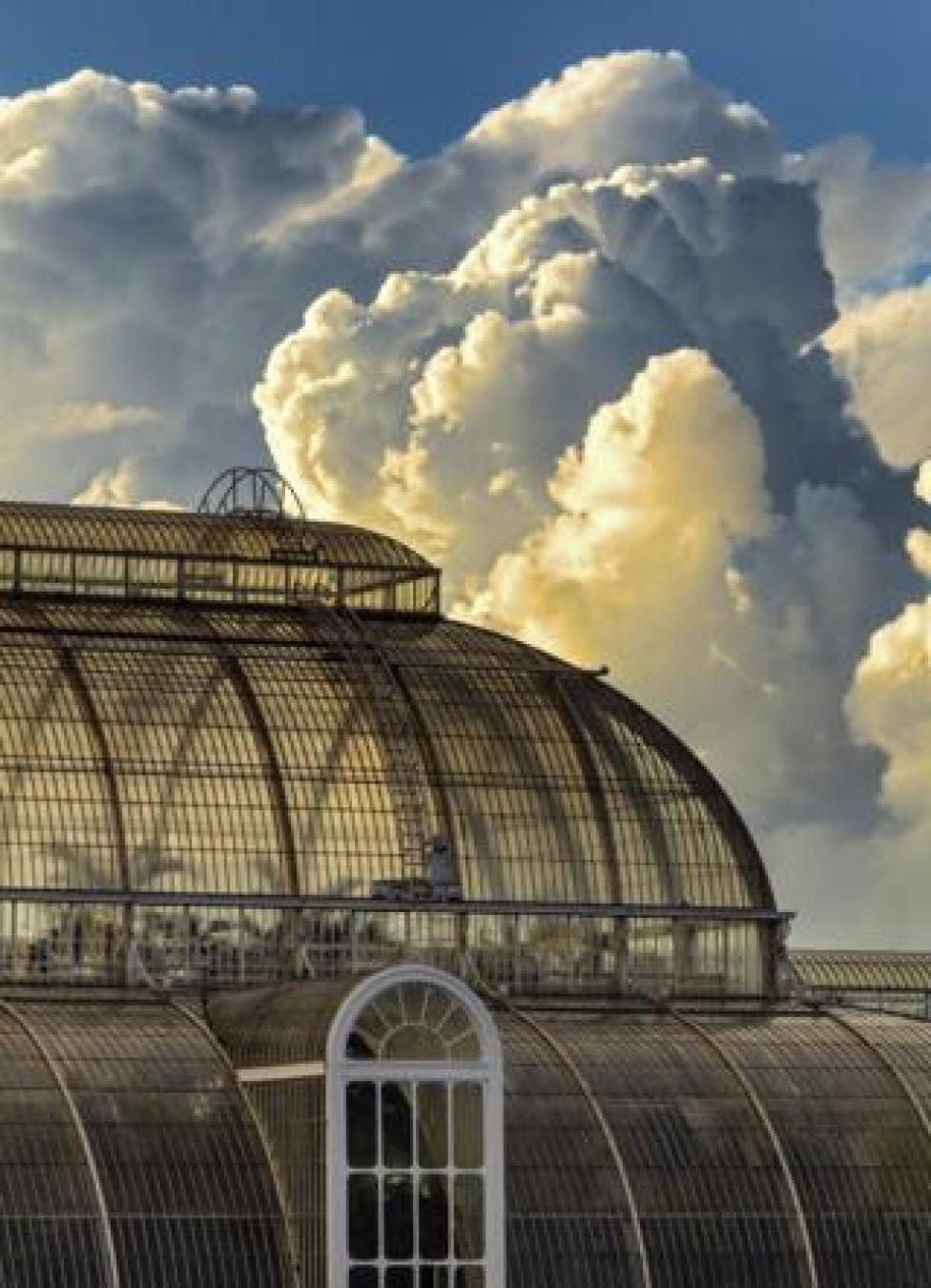 A very large greenhouse with the sky behind it