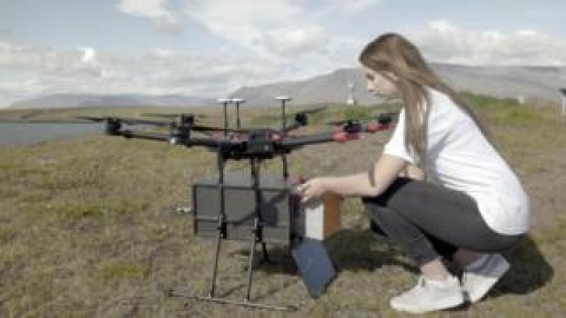 A woman loads sushi into a drone