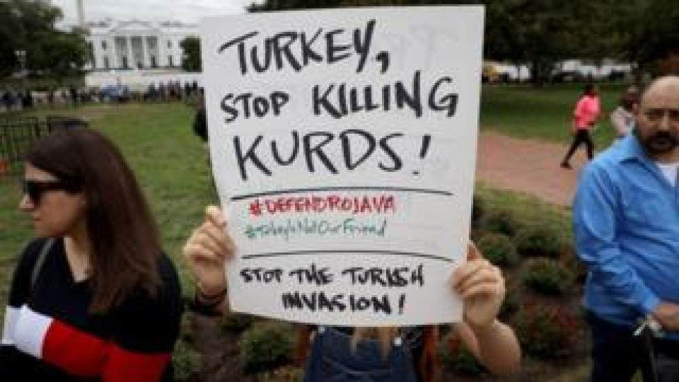 Protesters against Turkey's cross-border offensive in northern Syria wave signs outside the White House in Washington DC